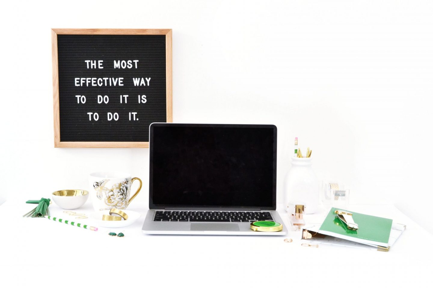 Laptop with green and white stationary next to it and motivational wall picture.
