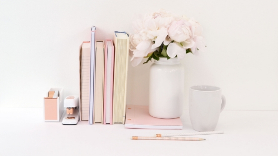 books, white roses in vase, stapler and candle on a shelf