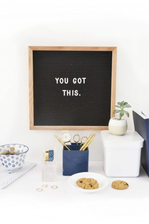 Message board above desk with blue and white themed stationary.