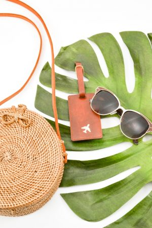 Large palm leaf with sunglasses, luggage tag and beach bag on top
