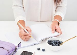 Lady writing in a notebook with blueberries on the table and a purple wallet