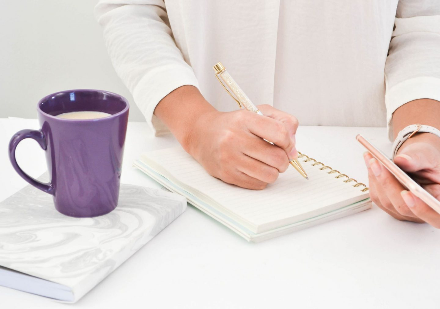 Purple cup of tea, lady using her mobile and writing notes in a notebook
