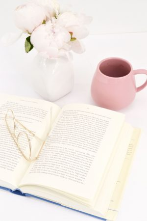 Open book with glasses on top, pink mug and white vase with flowers by the side.