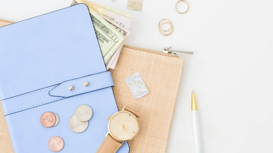 blue wallet, dollar notes, watch and pen on table