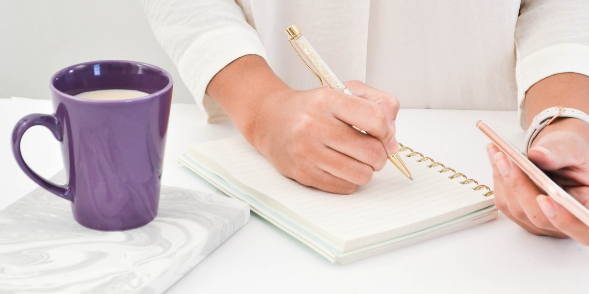 Lady writing in a notepad with purple mug on the table.
