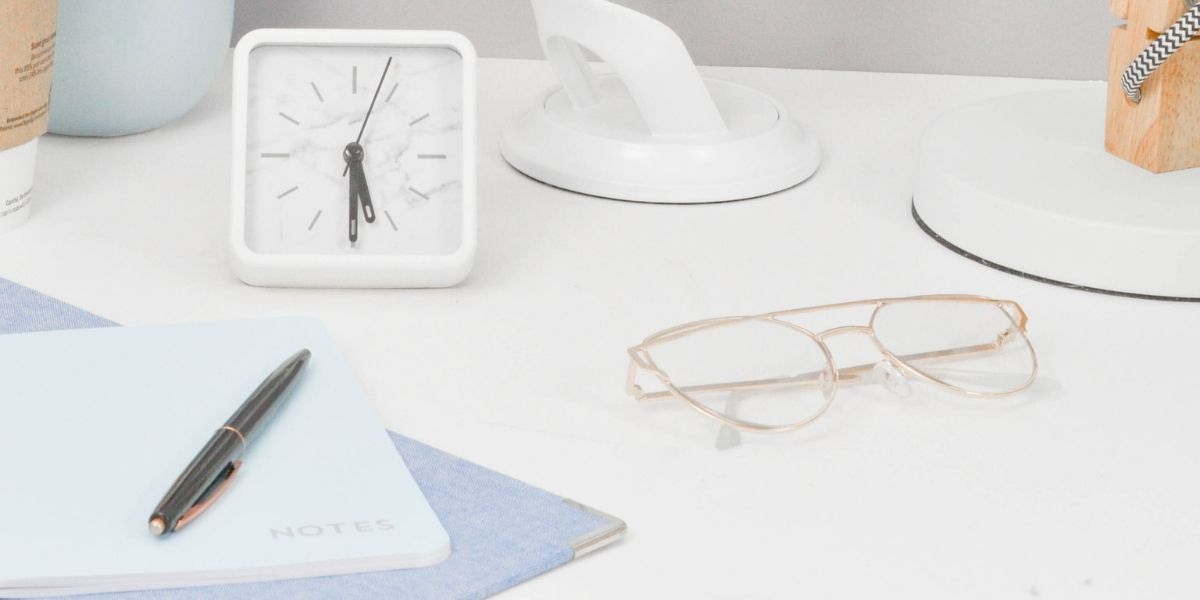 Clock, glasses and notepad on desk